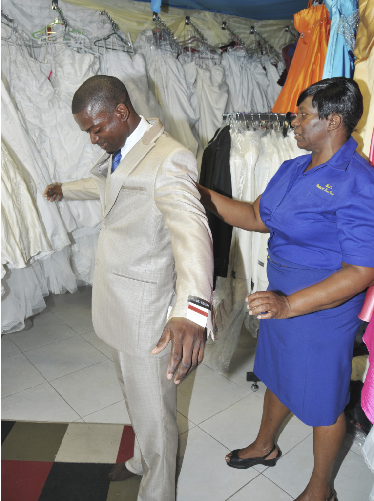 JNSBL client Karlene Campbell-Blair (right) adjusts a suit on a customer at her bridal store, Angels Bridal in May Pen, Clarendon. Campbell-Blair runs a bridal store, a flower shop and a clothes shop in the May Pen Market.